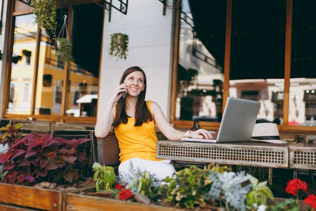 Niña feliz en el café de la calle al aire libre sentado en la mesa con la computadora portátil, hablando por teléfono móvil, manteniendo una conversación agradable, en el restaurante durante el tiempo libre