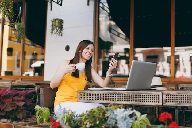 Niña feliz en la cafetería de la calle al aire libre sentado en la mesa con la computadora portátil, mensaje de texto en el teléfono móvil, beber té en el restaurante durante el tiempo libre