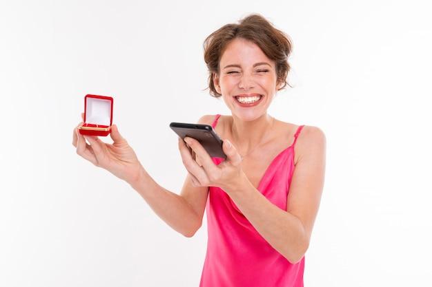 Niña feliz con caja con anillo de compromiso llamando a contar noticias a un amigo sobre fondo blanco.