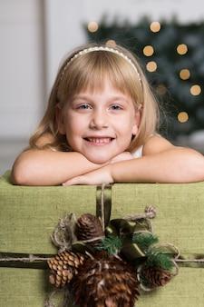 Niña feliz con una caja grande con un regalo sobre su cabeza. vacaciones de invierno, navidad y concepto de personas