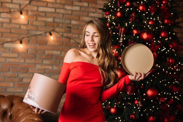 Niña feliz con caja de regalo en las manos. año nuevo presente, compras de invierno