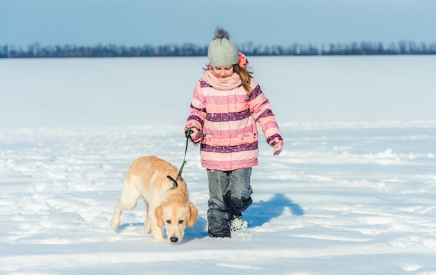 Niña feliz caminando con perro
