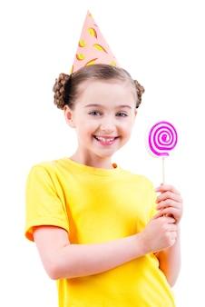 Niña feliz en camiseta amarilla y gorro de fiesta con dulces de colores - aislados en blanco.