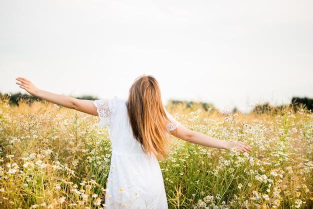 Niña feliz en el campo de la manzanilla, puesta de sol de verano. con un vestido blanco. corriendo y girando, el viento en mi cabello, estilo de vida. concepto de libertad y verano caluroso.