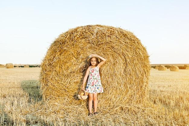 Niña feliz en el campo de trigo con pan