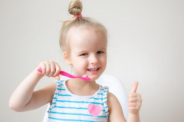 Niña feliz cepillando sus dientes, cepillo de dientes rosa, higiene dental, estilo de vida saludable concepto de estilo de vida
