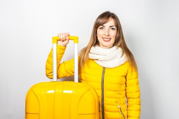 Niña feliz en una chaqueta amarilla sostiene el asa de una maleta amarilla