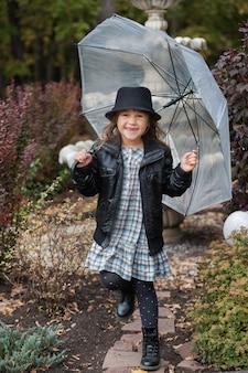 Niña feliz en chaqueta de cuero con paraguas en el parque otoño