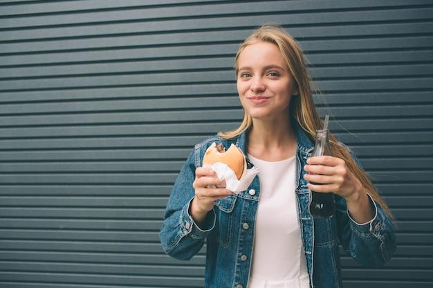 Niña feliz come comida rápida y bebe cola cerca de la pared gris