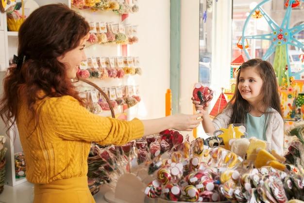 Niña feliz comprando dulces en la tienda