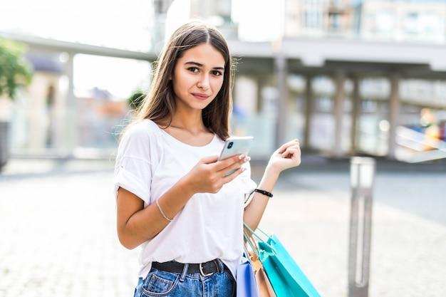 Niña feliz en compras saliendo del centro comercial con bolsas y mirando el teléfono.