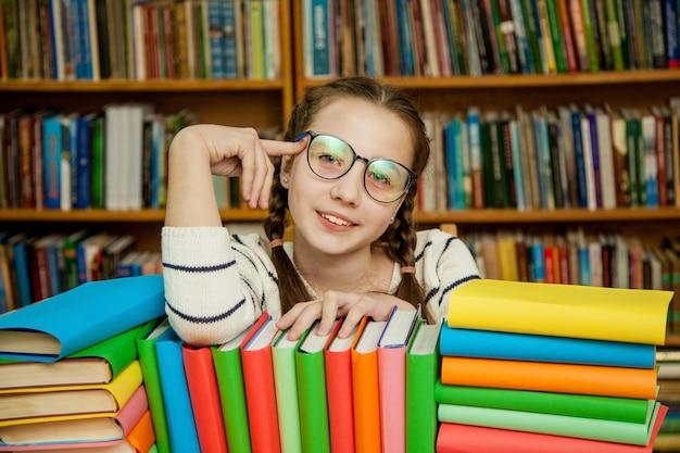 Niña feliz en copas con libros en la biblioteca