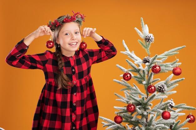 Niña feliz con corona de navidad en camisa a cuadros sosteniendo bolas de navidad