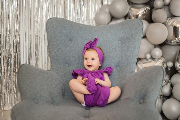 Una niña feliz en una diadema púrpura está sentada en una silla sobre fondo de globos grises