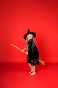 Niña feliz en un disfraz de bruja con un sombrero en una escoba en una pared roja aislada con espacio para texto
