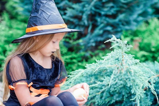 Niña feliz en disfraz de halloween con calabaza jack.trick o convite