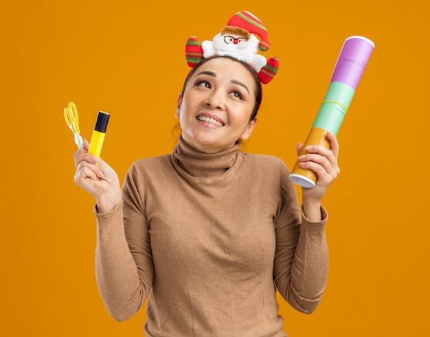 Niña feliz en divertido borde navideño en la cabeza sosteniendo petardos tijeras y pegamento