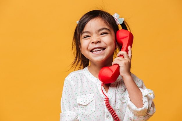 Niña feliz emocionada hablando por teléfono retro rojo.