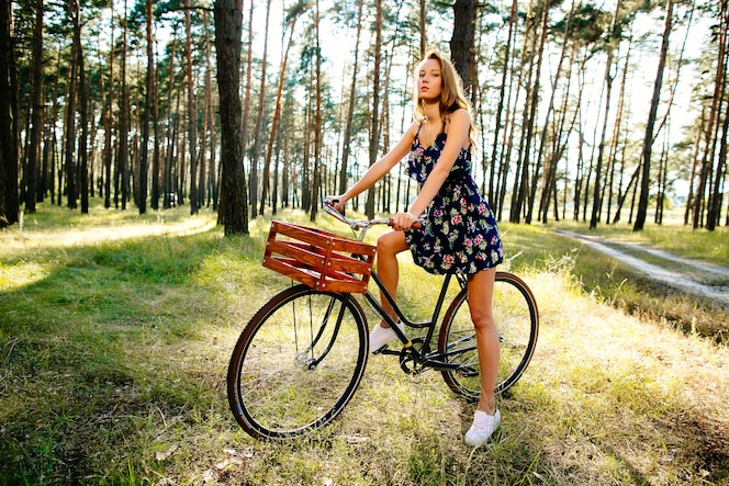Niña feliz en una bicicleta con una cesta en el bosque.