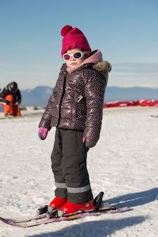 Niña feliz esquiando cuesta abajo