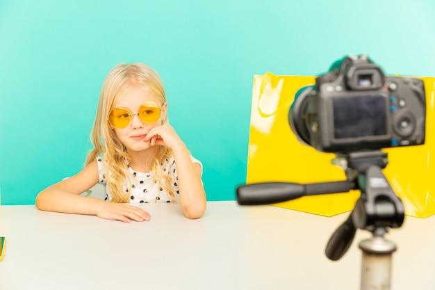 Niña feliz en el estudio azul hablando frente a cámara para vlog. trabajando como blogger, grabando video tutorial para internet.