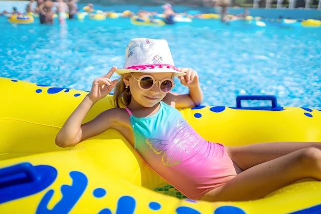 Niña feliz con gafas de sol y sombrero en la piscina exterior de lux