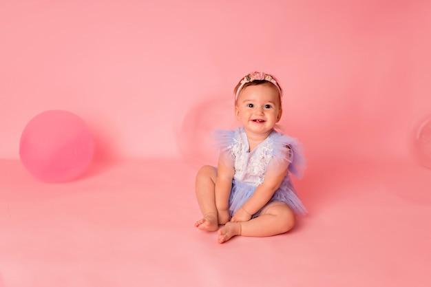 Niña feliz con globos sobre un fondo rosa celebra su primer cumpleaños