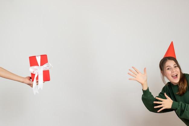 Niña feliz con gorro de fiesta mostrando regalo en mano humana sobre blanco
