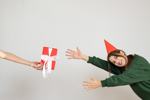 Niña feliz con gorro de fiesta tratando de atrapar el regalo en la mano humana sobre blanco