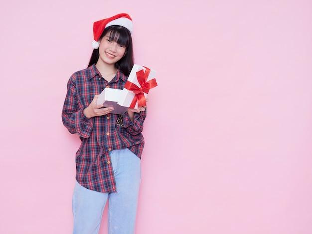 Niña feliz con gorro de papá noel abriendo una caja de regalo contra la pared rosa