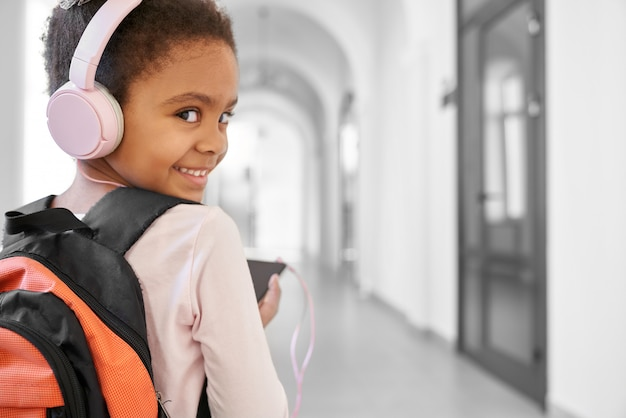 Niña feliz en grandes auriculares rosados escuchando música