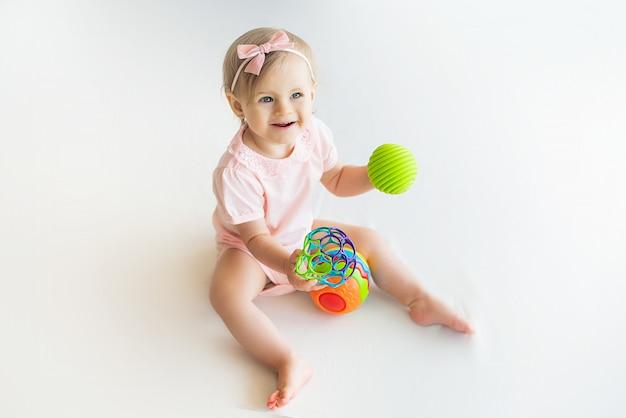 Niña feliz guardería jugando con pelota de goma colorida en casa