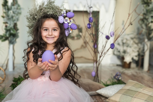 Niña feliz en guirnalda de flores con huevo de pascua