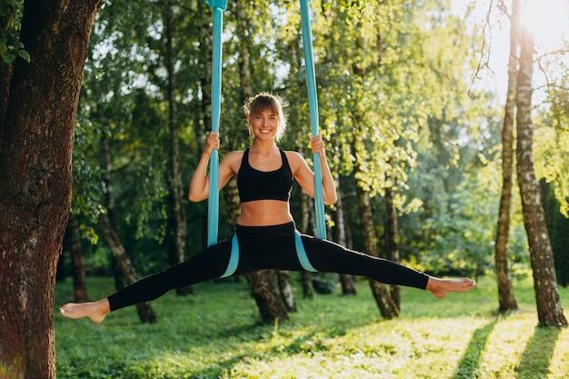 Niña feliz haciendo yoga al aire libre, extendiendo sus piernas bien separadas mirando a la cámara