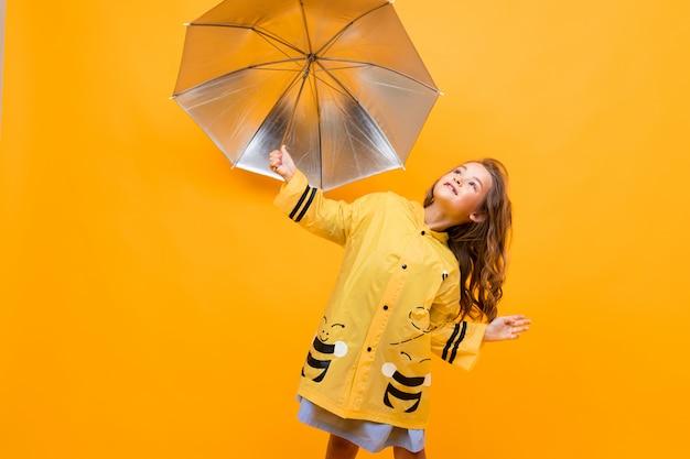 Niña feliz en un hermoso impermeable amarillo en forma de abeja sostiene un paraguas plateado y se encuentra sobre un fondo amarillo