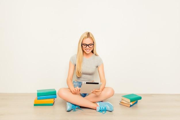 Niña feliz inteligente preparándose para los exámenes y usando tableta