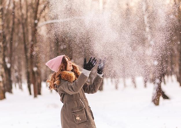 Niña feliz juega con nieve en el parque