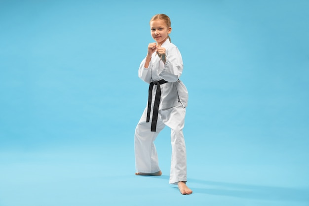 Niña feliz en kimono blanco mirando a la cámara mientras entrenaba