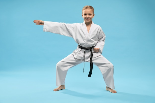 Niña feliz en kimono blanco de pie en posición universal