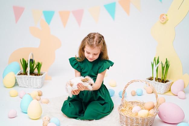 Niña feliz con lindo conejito esponjoso cerca de huevos de pascua pintados