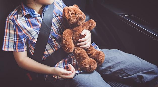 Niña feliz, llevando, cinturones de seguridad, en coche