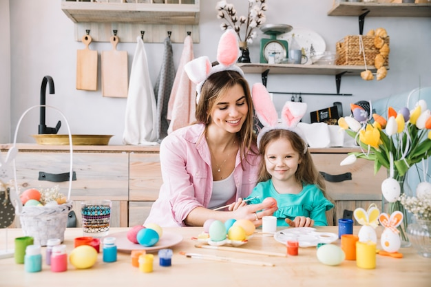 Niña feliz con la madre pintando huevos para pascua