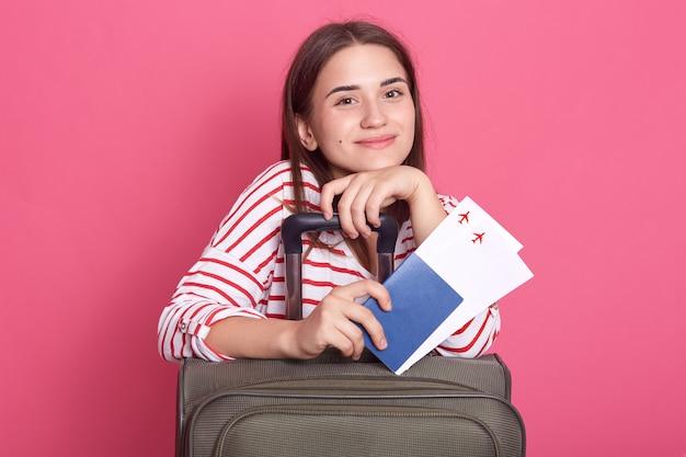 Niña feliz con maleta y pasaporte aislado sobre pared rosa, chica de cabello oscuro con camisa a rayas, vistiendo camiseta casual a rayas, lista para viajar.