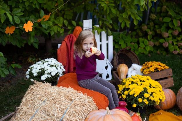 Niña feliz con manzana al aire libre otoño