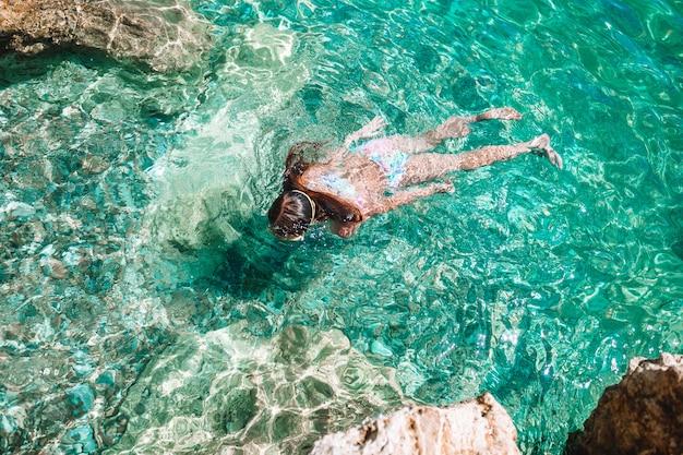 Niña feliz en máscara de snorkel buceo bajo el agua con peces tropicales