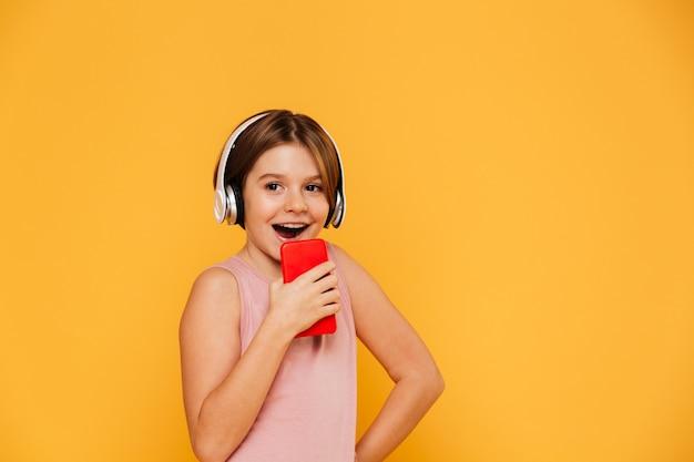 Niña feliz mirando a un lado mientras usa auriculares y cantando en smartphone aislado