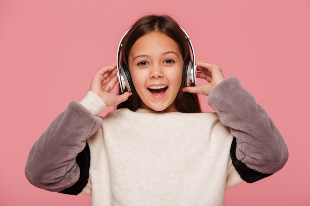 Niña feliz mirando mientras se escucha música en los auriculares aislados
