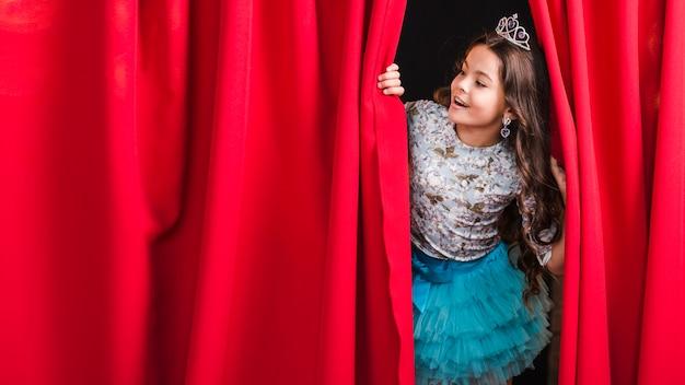 Niña feliz mirando a través de la cortina roja en el escenario