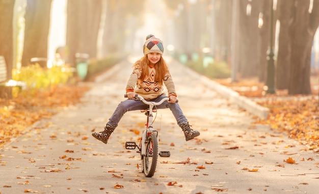 Niña feliz montando bicicleta en el parque