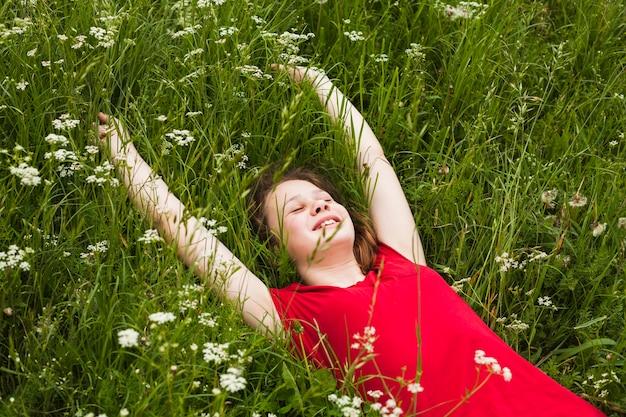Niña feliz con los ojos cerrados, tumbado en la hierba en la hermosa naturaleza